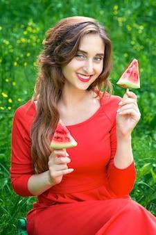 La donna tiene due pezzi di anguria.