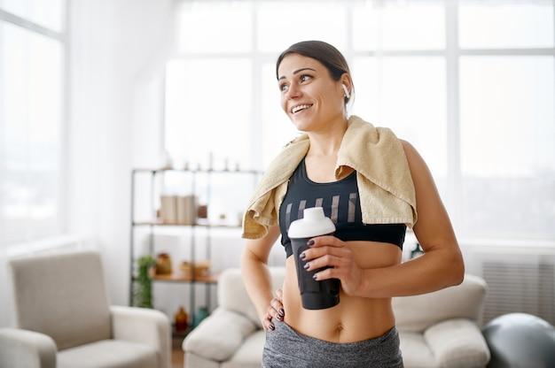 La donna tiene la bottiglia d'acqua dopo l'allenamento. persona di sesso femminile in abbigliamento sportivo, allenamento sportivo internet, interno della stanza