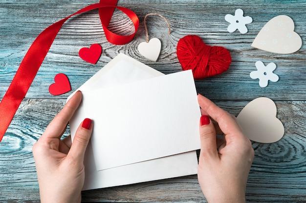 Una donna tiene una busta bianca con una lettera vuota su uno sfondo romantico con cuori e a