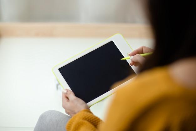 La donna tiene la compressa bianca con la penna. ministero degli interni mentre auto-isolamento, lavoro da casa. formazione online, e-learning durante la quarantena.