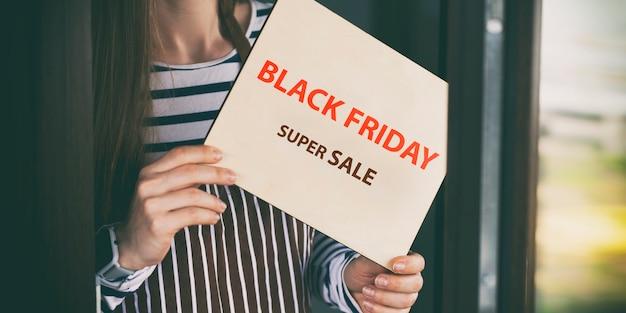 La donna tiene il cartello in legno con il testo: vendita venerdì nero