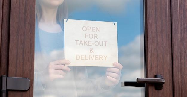 La donna tiene il cartello in legno con testo: aperto per asporto e consegna
