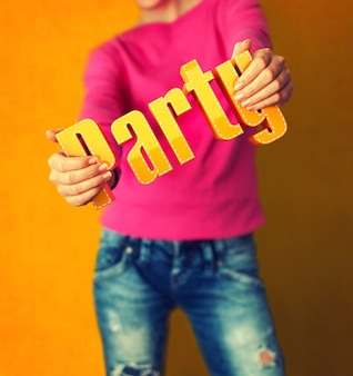 La donna tiene la parola party su una parete colorata luminosa
