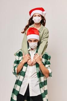 Una donna con un cappello da festa si siede sulle spalle di un uomo con una maschera medica