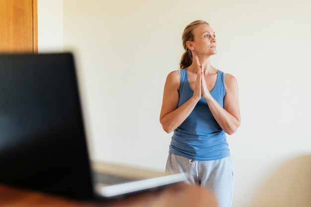Donna a casa che fa yoga durante la quarantena