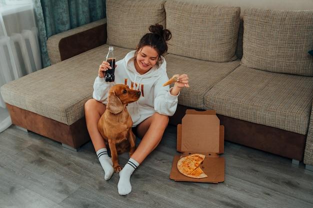 Una donna a casa mangia la pizza, insieme a un cane cocker spaniel, un animale domestico