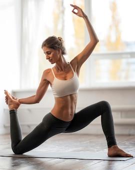 Donna a casa che esercita yoga