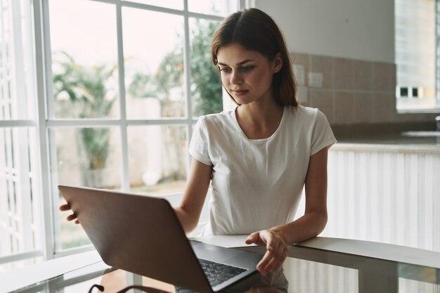 Donna a casa davanti al computer portatile al tavolo lavoro ufficio internet professionale