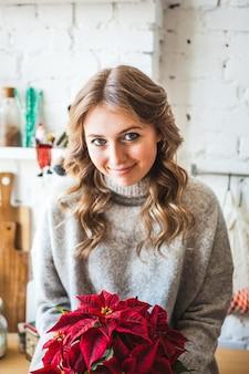 Donna a casa che tiene un fiore di natale nelle sue mani