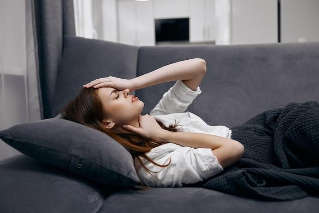 La donna a casa si trova sul divano coperto da una coperta sensazione di malessere mano sul viso