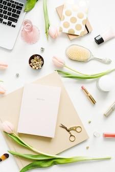 Area di lavoro scrivania donna home office con laptop, fiori di tulipano rosa, taccuino, accessori e cosmetici su bianco