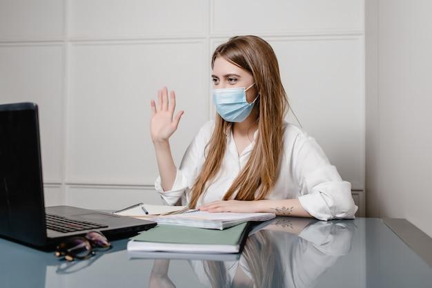 Ufficio della donna a casa con la maschera d'uso del computer portatile e studiare online