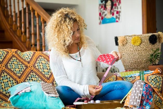 Donna a casa seduta sul divano che lavora con maschera di protezione medica fatta a mano per il coronavirus