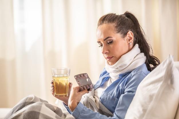 La donna nel trattamento domiciliare controlla il blister della medicina che tiene una tazza di tè calda nell'altra mano.