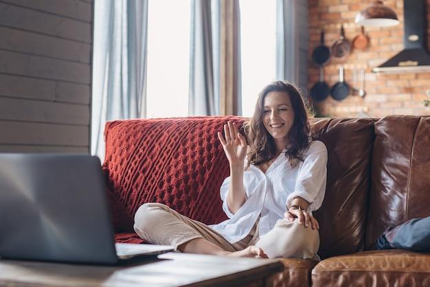 Donna a casa che saluta mentre fa una videochiamata sul computer portatile.