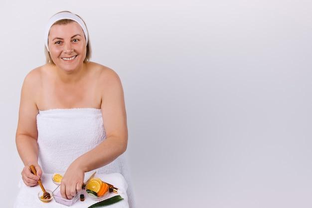 Una donna a casa, avvolta in un asciugamano bianco con un sorriso, prepara una maschera viso e corpo con prodotti naturali. sfondo bianco e spazio laterale vuoto. foto di alta qualità