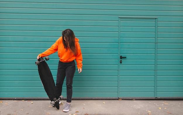 La donna in felpa con cappuccio sta con un longboard nelle sue mani