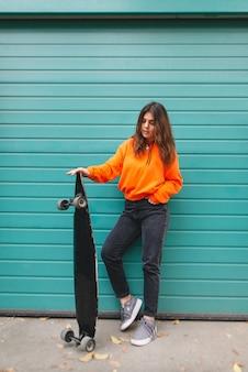 La donna in felpa con cappuccio sta con un longboard