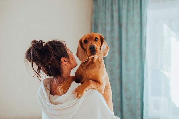 La donna di casa tiene in braccio un cane, di razza cocker spaniel inglese