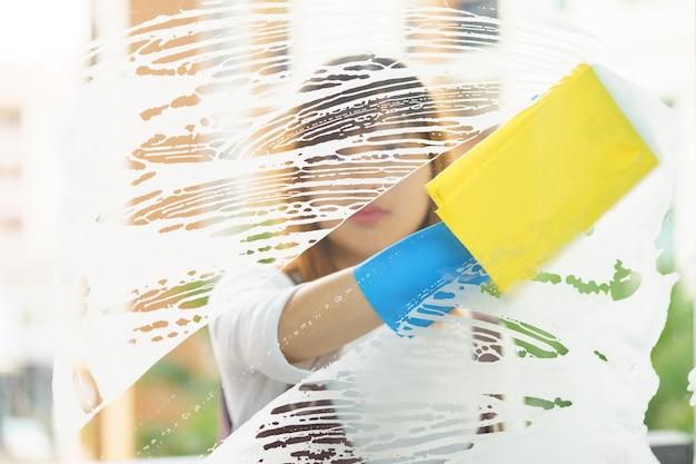 Governante della donna che pulisce lo specchio con la spugna gialla