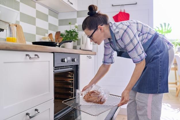 Donna casalinga in grembiule che prepara carne di maiale in una manica da forno a casa, mette il vassoio di carne nel forno