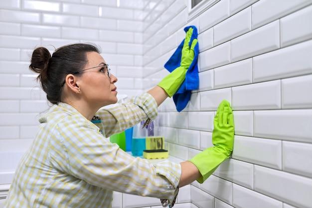 Casalinga della donna che fa la pulizia della casa in bagno lucidatura parete piastrellata femminile in bagno con panno in microfibra