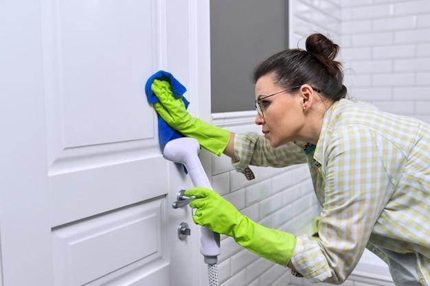 Casalinga della donna che fa la pulizia della casa in bagno, porta di lavaggio femminile con vapore della doccia. utilizzo del pulitore a vapore per una pulizia rapida