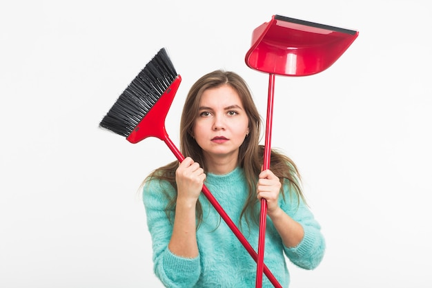 Donna o casalinga che tiene scopa, stanco di pulire, sul muro bianco, isolato con lo spazio della copia.