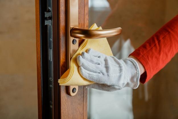 La donna domestica in guanti bianchi pulisce la manopola della porta dallo straccio del panno nuovo normale coronavirus covid 19 nella disinfezione delle superfici. pulizia della maniglia della porta anteriore con detergente alcolico antibatterico.