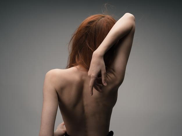 Donna che si abbraccia con le mani indietro vista modello schiena nuda.