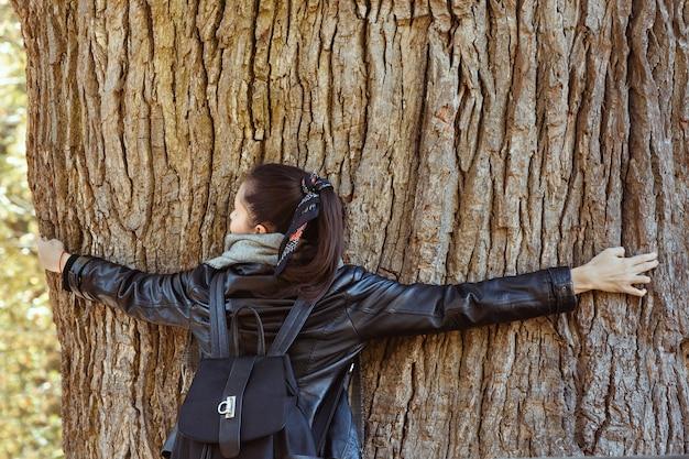 Donna che abbraccia il tronco d'albero enorme. albero perenne.