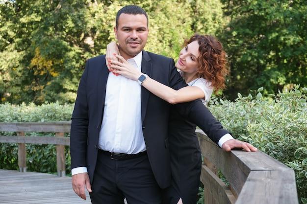 La donna abbraccia un uomo e lo guarda con uno sguardo amorevole. marito e moglie felici.