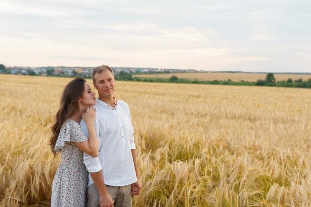 La donna abbraccia l'uomo, camminando su un campo di grano. coppia d'amore, relazione romantica
