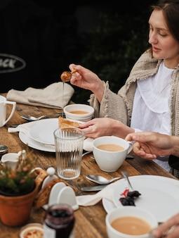 La donna impone il pane al miele, usando i cucchiai per miele specifico. colazione in natura