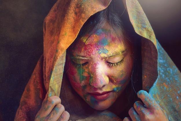 La donna in abito indiano si sta godendo la polvere colorata nel festival di holi.holi festival of colours india.stlye vintage