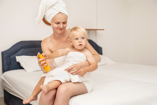 La donna e il bambino neonato in asciugamani bianchi dopo il bagno applicano la crema solare o la crema solare dopo il sole