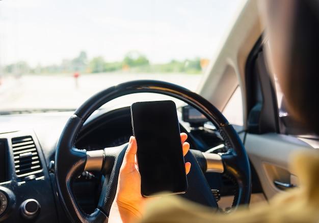 Donna all'interno di un'auto e utilizzando una mano che tiene lo schermo vuoto dello smartphone mobile mentre si guida l'auto