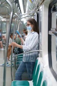 La donna all'interno dell'auto della metropolitana indossa una maschera chirurgica per proteggersi dall'infezione da covid usando lo smartphone