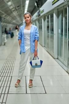 Donna all'interno della metropolitana in attesa sulla piattaforma di una stazione ferroviaria per l'arrivo del treno.