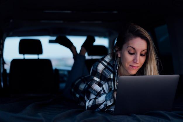 Donna all'interno del furgone con il computer portatile in viaggio per le vacanze in viaggio divertendosi a guardare i video all'interno del furgone