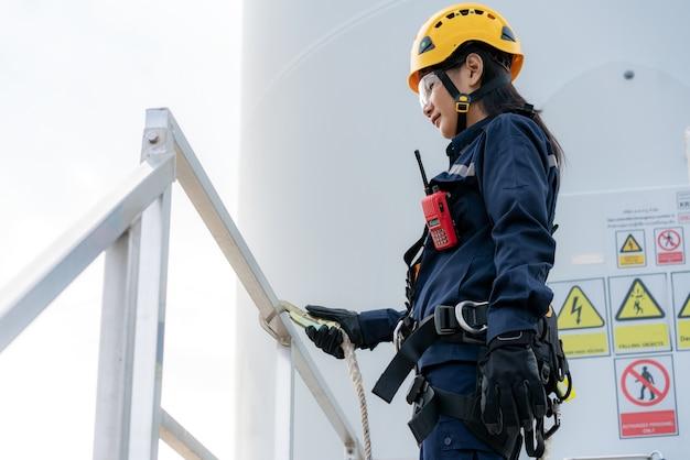 Donna ingegnere di ispezione che indossa imbracatura di sicurezza e linea di sicurezza