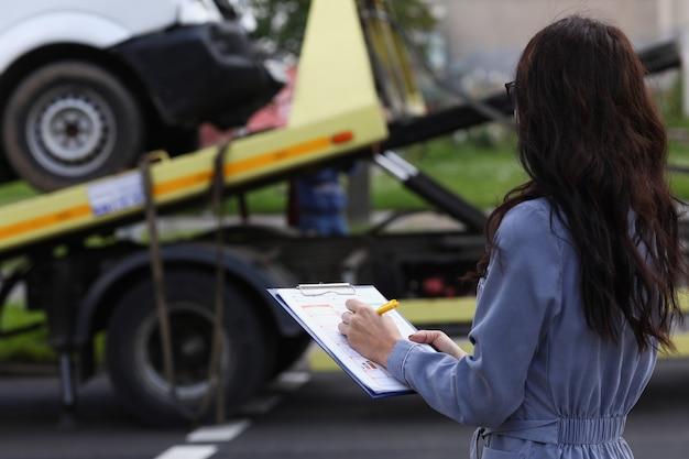 L'agente di assicurazione donna prepara i documenti per l'auto che viene portata via dal carro attrezzi