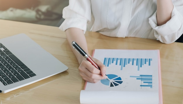 Consulente di investimento della donna che analizza la dichiarazione di bilancio del rapporto finanziario annuale dell'azienda che lavora con i grafici dei documenti