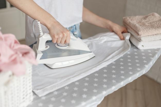Donna che stira la camicia bianca lavata clead a casa. cestino di vimini e pila di asciugamani di colore sull'asse da stiro