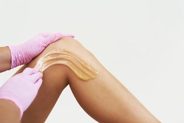 La donna sta applicando la pasta per l'epilazione. procedura di depilazione su bianco.
