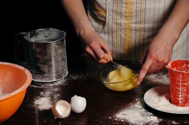 Una donna sta sbattendo le uova in una ciotola. torta di cottura, biscotto, fegato.
