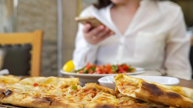La donna sta navigando sul telefono durante il pranzo seduto a tavola con cibo gustoso, primo piano delle mani su sfondo sfocato. pranzo tradizionale azero con pane khachapuri ripieno di formaggio e verdure.