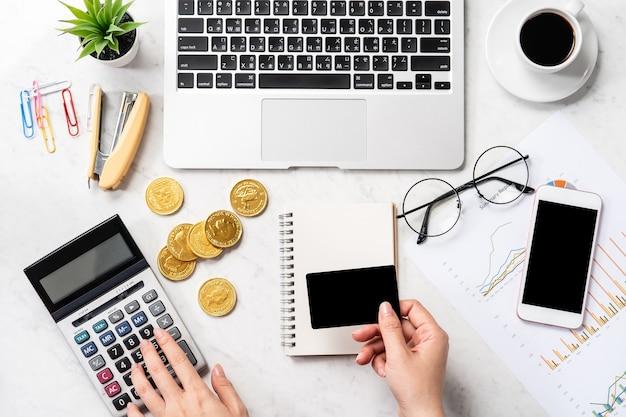 Una donna sta calcolando la quota, il profitto e sta effettuando un pagamento online su un moderno tavolo da ufficio in marmo, mock up, vista dall'alto, copia spazio, piatto laici
