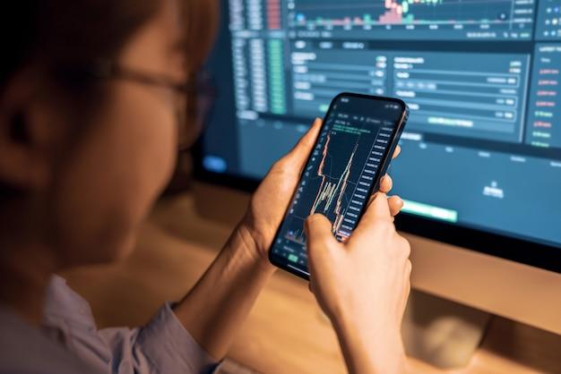 La donna sta controllando il grafico dei prezzi bitcoin sullo scambio digitale su smartphone