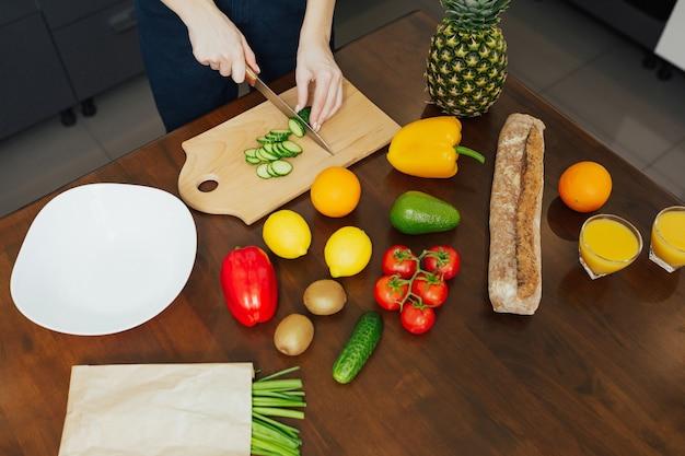 Donna sta tagliando verdure biologiche fresche sulla tavola di legno mentre cucina la cena in cucina